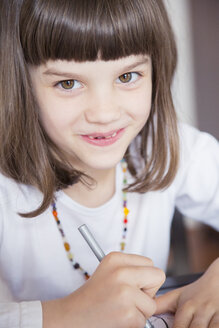 Portrait of smiling little girl painting with wax crayon - LVF001218