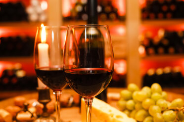 Two glasses of red wine, lightes candle, grapes and bottle in private wine cellar - JTF000549