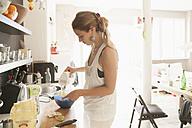 Young woman mixing dough at kitchen - TCF004009