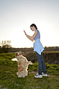 Young woman with Golden Retriever on meadow - BFRF000420