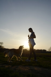 Young woman training Golden Retriever on meadow at sunset - BFRF000422