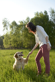 Golden Retriever giving young woman a paw - BFRF000427