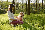 Young woman sitting with Golden Retriever on meadow - BFRF000433