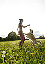 Young woman playing with Golden Retriever on meadow - BFRF000440
