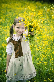 Little girl wearing country style dress presenting bunch of buttercups, Ranunculus, on meadow - SARF000596