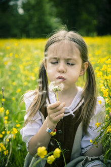 Little girl wearing country style dress blowing blowball on meadow - SARF000598