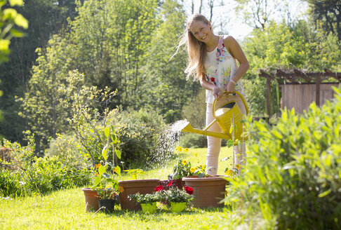 Portrait of smiling teenage girl watering potted plants in the garden - WWF003294