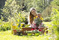 Portrait of smiling teenage girl repotting plants in the garden - WWF003296