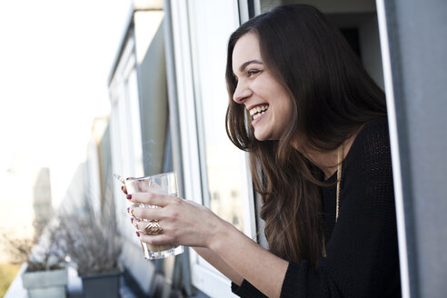Woman with glass and cigarette leaning out a window - FEXF000073