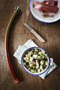 Cooking pot of sliced rhubarb on cloth, kitchen knife and plate of rhubarb peel on wood - EVGF000571