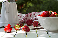 Bowl of strawberries, knife, kitchen towel and jar on white wood - LVF001244