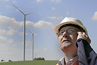 Germany, technician with safety helmet in front of wind turbines - SGF000680
