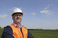Germany, portrait of smiling technician with safety helmet in front of wind turbines - SGF000682