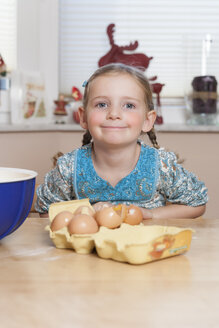 Portrait of little girl sitting at kitchen table - ECF000622