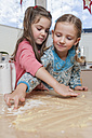 Portrait of two little girls with leftovers of dough on kitchen table - ECF000627