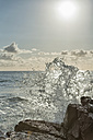 Australia, New South Wales, Tweed Shire, splashing breakwater at the rocky shore of Hastings Point in the first morning light - SHF001271