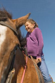 Australia, New South Wales, Dorrigo, girl  sitting on a horse, partial view - SHF001331