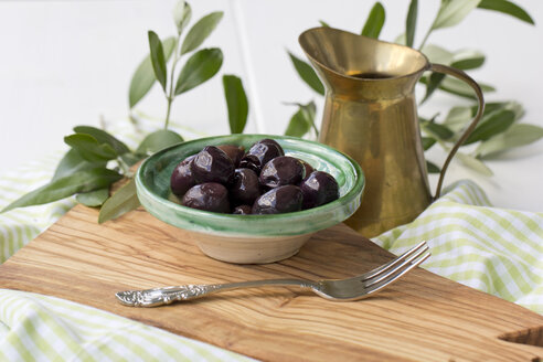 Bowl of black olives and fork on board made of olive wood - YFF000135