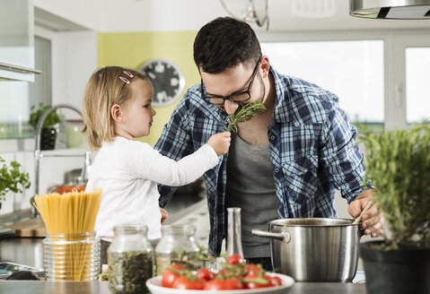 Father and daughter cooking in kitchen - UUF000480