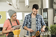 Couple cooking in kitchen at home - UUF000489