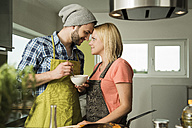Couple in love cooking in kitchen at home - UUF000522