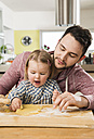 Father and daughter baking in kitchen - UUF000512