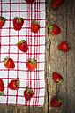 Strawberries on kitchen towel and dark wood - LVF001254
