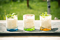 Three garnished glasses of curd with herbs on wooden tray - SARF000619