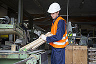 Young worker at carpentry of pallet production - SGF000690