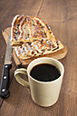 Cup of black coffee, knife and Danish pastry with marzipan on wooden board and table - CSTF000358