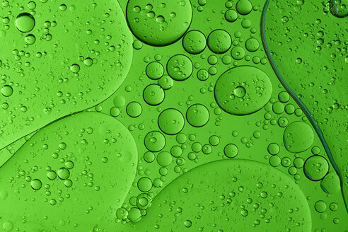 Oil and water in front of green background - MJOF000161