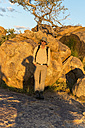 Africa, Namibia, Erongo mountains, hiker standing in front of rock at sunset - HLF000568