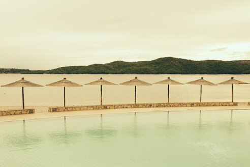 Croatia, Sibenik, Sunshades, Swimming pool of a hotel facility, Evening mood - MEMF000161