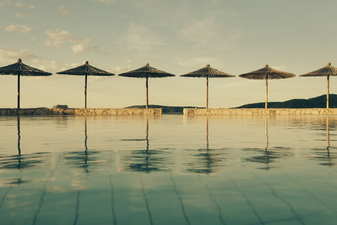Croatia, Sibenik, Sunshades, Swimming pool of a hotel facility, Evening mood - MEMF000166