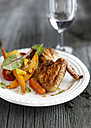 Plate of roasted chicken, cherry tomatoes, carrot, slices of sweet potato and maize on grey wood - KSWF001288