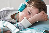 Portrait of smiling boy with headphones lying on beanbag - LVF001283