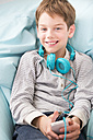 Portrait of smiling boy with smartphone and headphones lying on beanbag - LVF001288