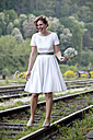 Laughing bride balancing on rail - ND000454
