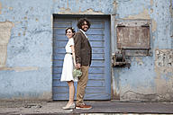 Bridal couple standing in front of an old industrial building - ND000458