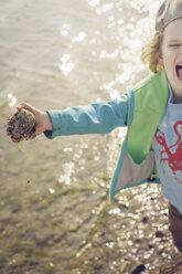 Germany, Mecklenburg-Western Pomerania, Ruegen, Screaming boy holding stone at the coast - MJF001172