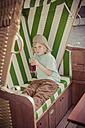 Germany, Mecklenburg-Western Pomerania, Ruegen, Boy in beach chair drinking soft drink - MJ001174