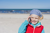 Germany, Mecklenburg-Western Pomerania, Ruegen, Schaabe, Boy on cell phone at the beach - MJF001220