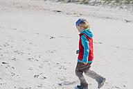 Germany, Mecklenburg-Western Pomerania, Ruegen, Schaabe, Boy walking on windy beach - MJF001224