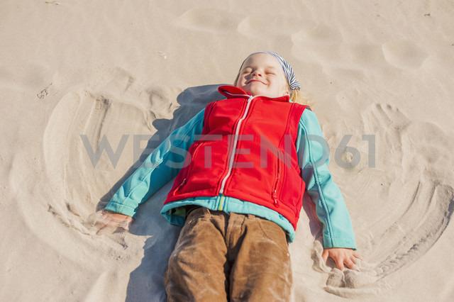 Germany, Mecklenburg-Western Pomerania, Ruegen, Schaabe, Boy lying in sand on beach - MJF001226