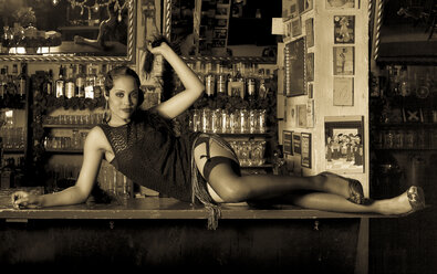 Portrait of young woman dressed in Twenties style lying on counter in bar - FC000222