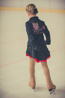 Young female figure skater on ice rink at competition, back view - MJF001272