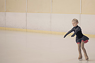 Young female figure skater moving on ice rink - MJF001277