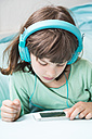 Portrait of little girl with headphones using smartphone - LVF001307