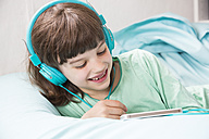 Portrait of little girl with headphones using smartphone - LVF001312