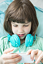 Portrait of little girl with headphones using smartphone - LVF001314